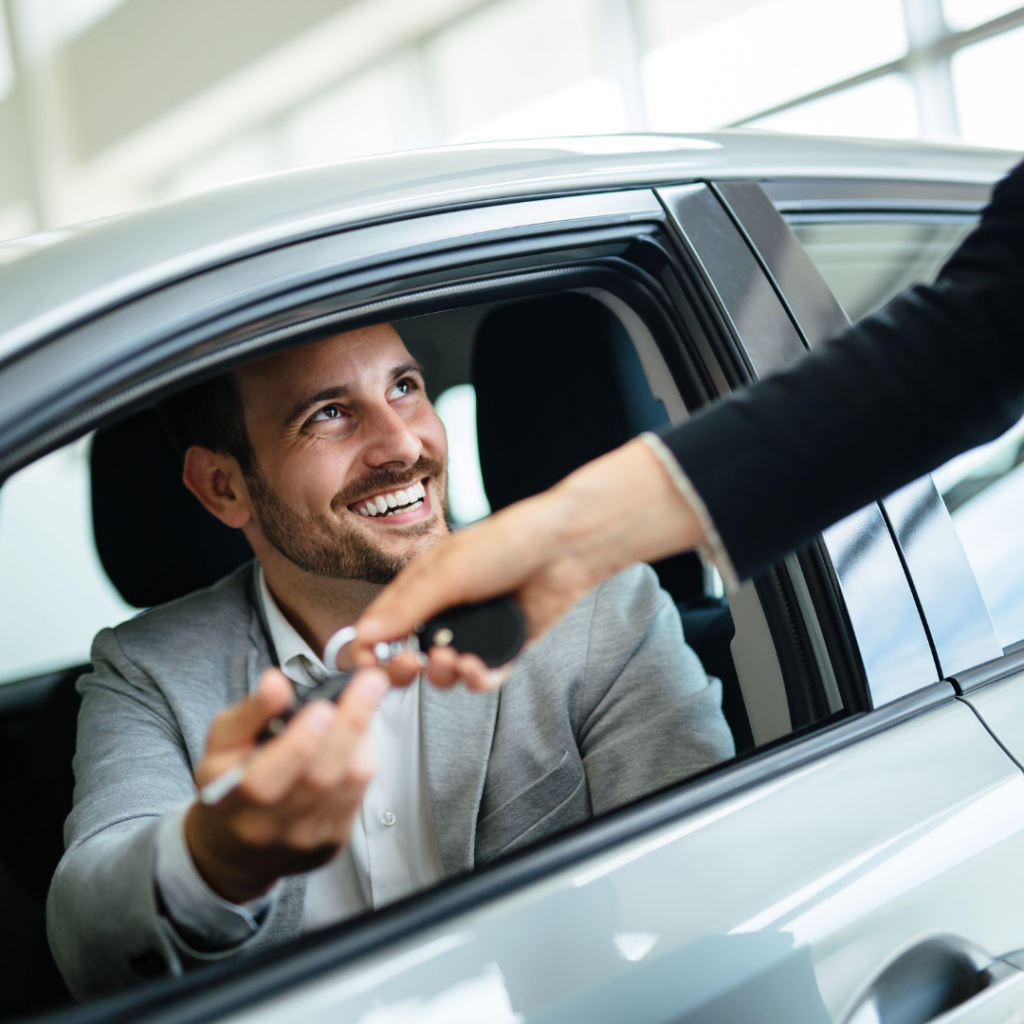 man being given keys to a second hand car